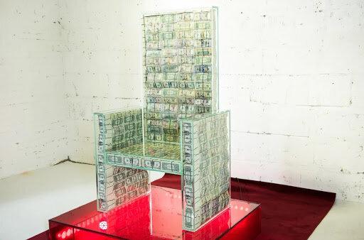 На фото аттракцион Денежный трон Х10: миллион настоящих долларов в бронированной стеклянной оболочке позволяют почувствовать мощную энергию денег тому, кто посидел на нём (всего за каких-то 600рублей).