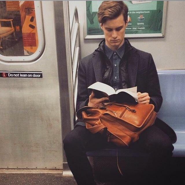 На фотографии: Молодой человек читает книгу в метро